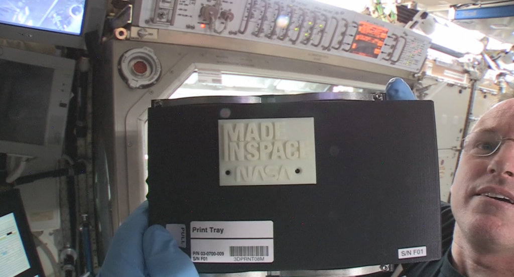 A Nemzetközi Űrállomás parancsnoka, Barry Wilmore bemutatja az első űrben 3D-s nyomtatással készített tárgyat. A nyomtatót november 17-én installálta, és november 25-én segítette a földi irányítókat az első nyomtatásnál. (Fotó: NASA)