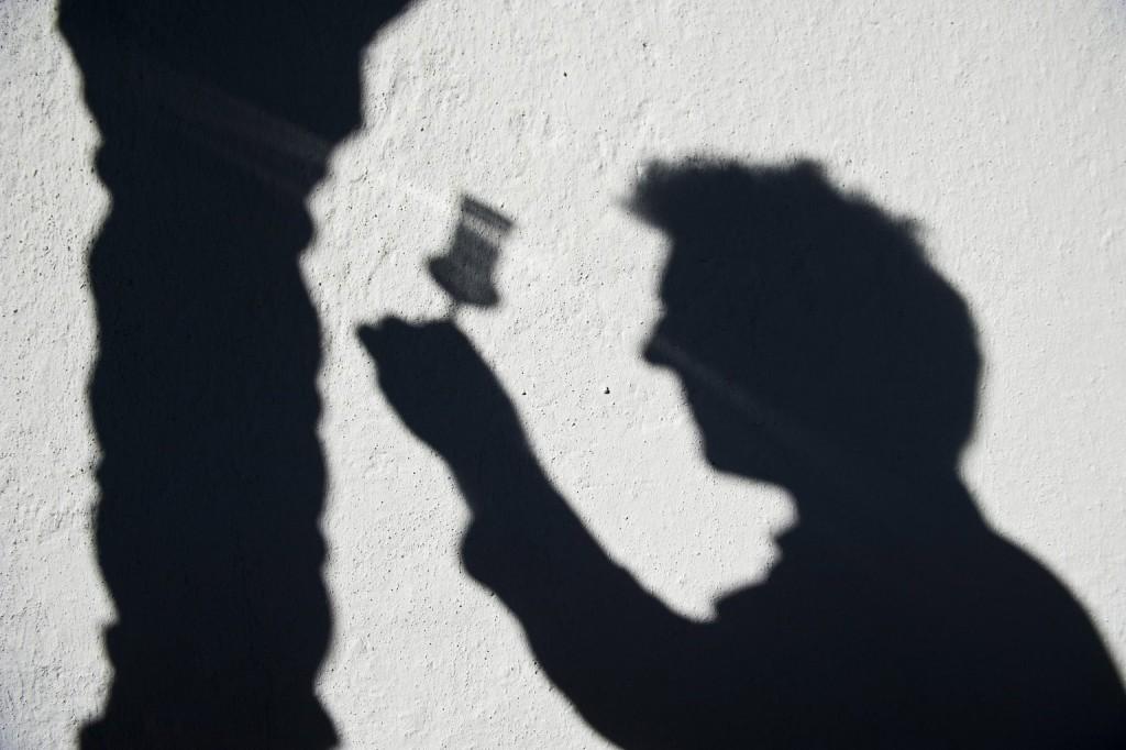 Pálinkát kóstoló férfi árnyéka a Szatmár-Beregi Pálinka Lovagrend Pálinkaházának falán Tarpán. (MTI-fotó: Balázs Attila)