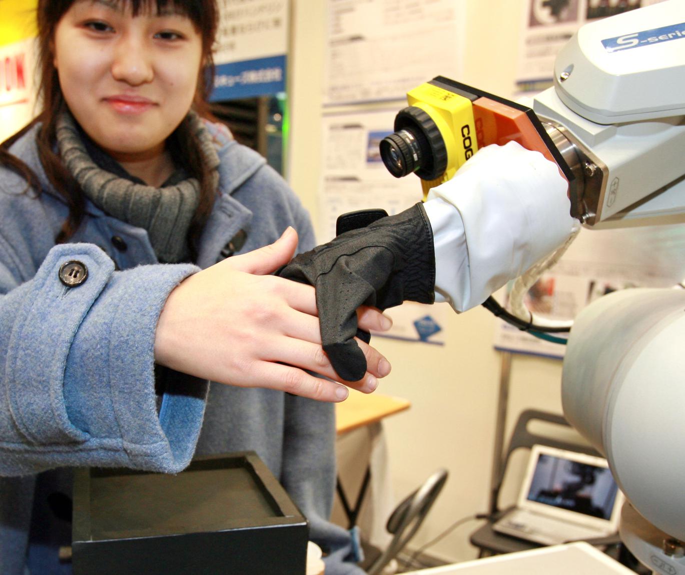 Egy látogató kezet ráz egy puha robotkézzel egy tokiói kiállításon 2009-ben. A Squse japán vállalat fejlesztette robotkéznek 21 mesterséges izma van pneumatikus működtető egységekkel, amelyekkel az ujj egyes ízületei behajlíthatóak és kinyújthatóak. Emellett CCD-kamerával szerelték fel, és az emberi kézhez hasonlóan képes megmarkolni a tárgyakat. (Fotó: AFP)