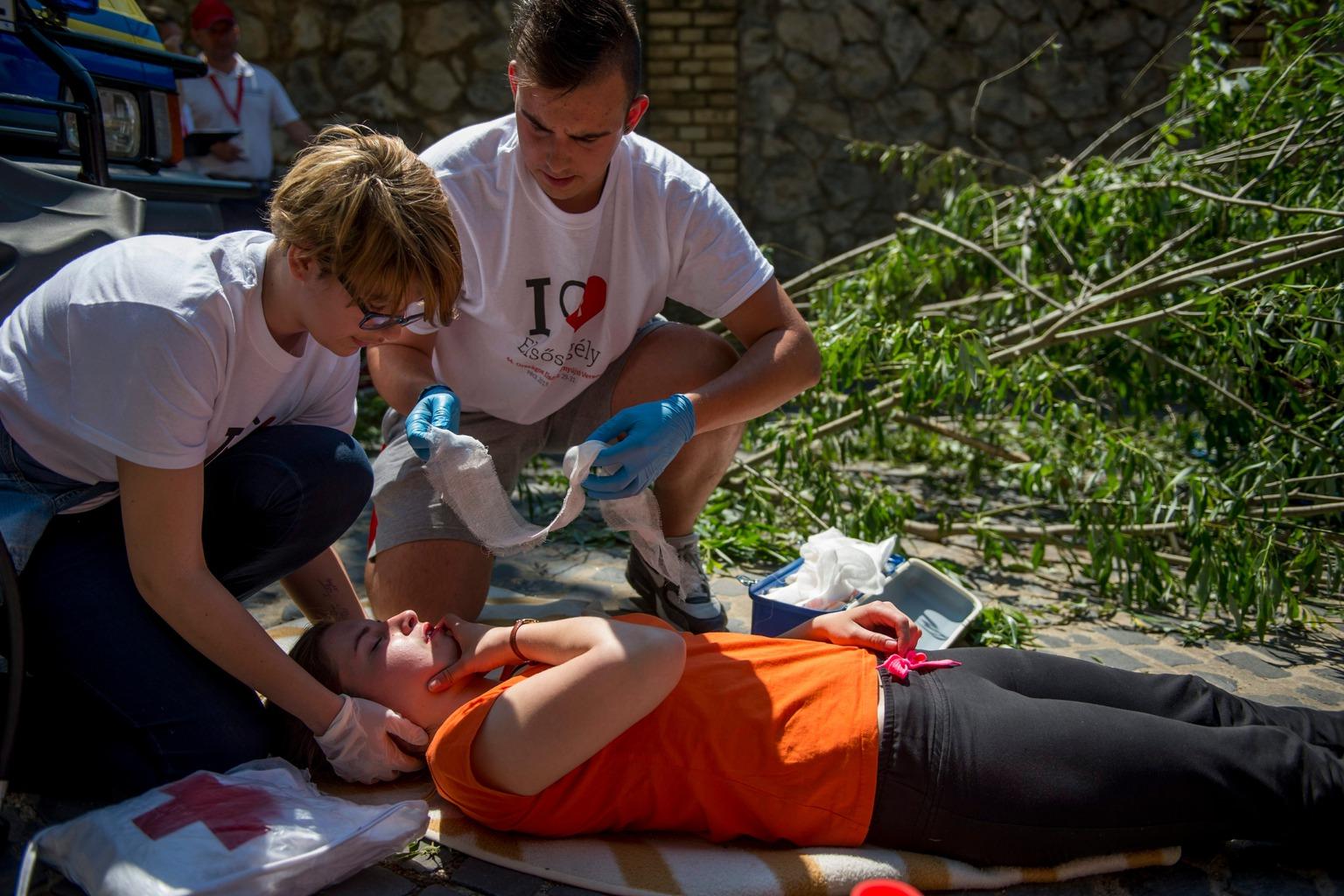 Pécs, 2015. május 30. Szimulált sérültet lát el egy csapat a Magyar Vöröskereszt 44. Országos Elsősegélynyújtó Versenyén Pécs belvárosában 2015. május 30-án. A megmérettetésen 56 csapatban 260 elsősegélynyújtó adott számot elméleti és gyakorlati elsősegély-nyújtási ismereteiről a baranyai megyeszékhely belvárosában kialakított húsz állomásos körpályán. MTI Fotó: Sóki Tamás