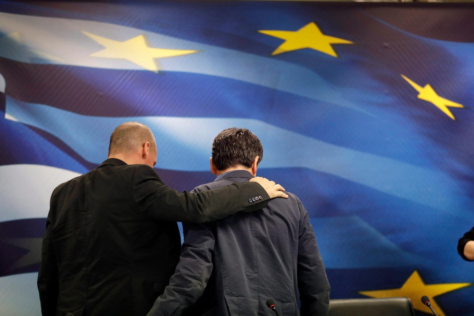 Jánisz Varufakisz lemondott görög pénzügyminiszter (b) és utódja, Evklídisz Cakalotosz a tisztség átadásán Athénban 2015. július 6-án, miután az előző nap a nemek győztek a Görögország nemzetközi hitelprogramjáról tartott népszavazáson. (MTI/AP/Petr David Josek)