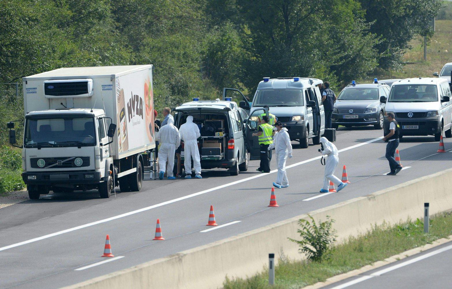 Védőruhába öltözött rendőrök egy teherautó mögött az A4-es autópályán Pandorf közelében 2015. augusztus 27-én. A teherautóban menekültek holttestére bukkantak.  Egyes sajtóértesülések szerint akár az ötvenet is elérheti a halottak száma. (MTI/EPA/Roland Schlager)