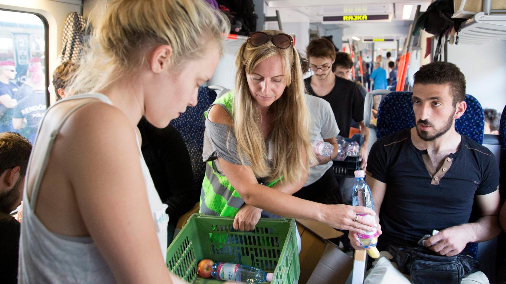 Győr, 2015. szeptember 14. Önkéntesek vizet és élelmet osztanak migránsoknak a Hegyeshalom felé tartó vonaton a győri vasútállomáson 2015. szeptember 14-én. MTI Fotó: Nyikos Péter
