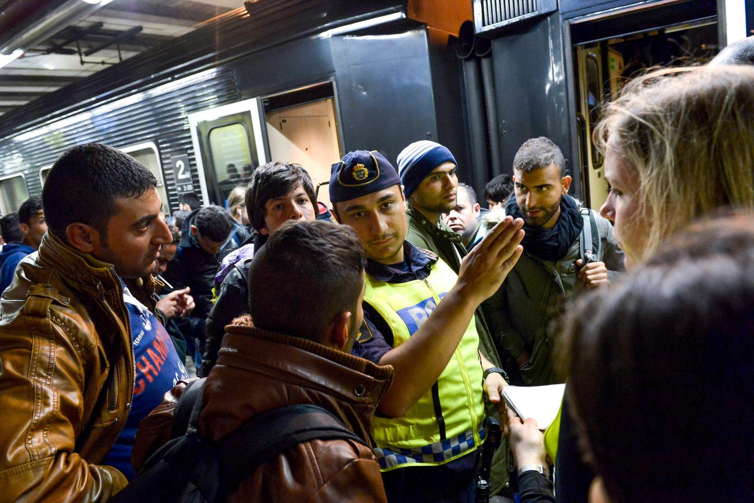 Stockholm, 2015. szeptember 12. Egy rendőr tájékoztatja a stockholmi pályaudvarra érkező illegális bevándorlókat 2015. szeptember 12-én. Ezen a napon mintegy 250 migráns érkezett vonattal a svéd fővárosba. (MTI/EPA/Jonas Ektsromer)