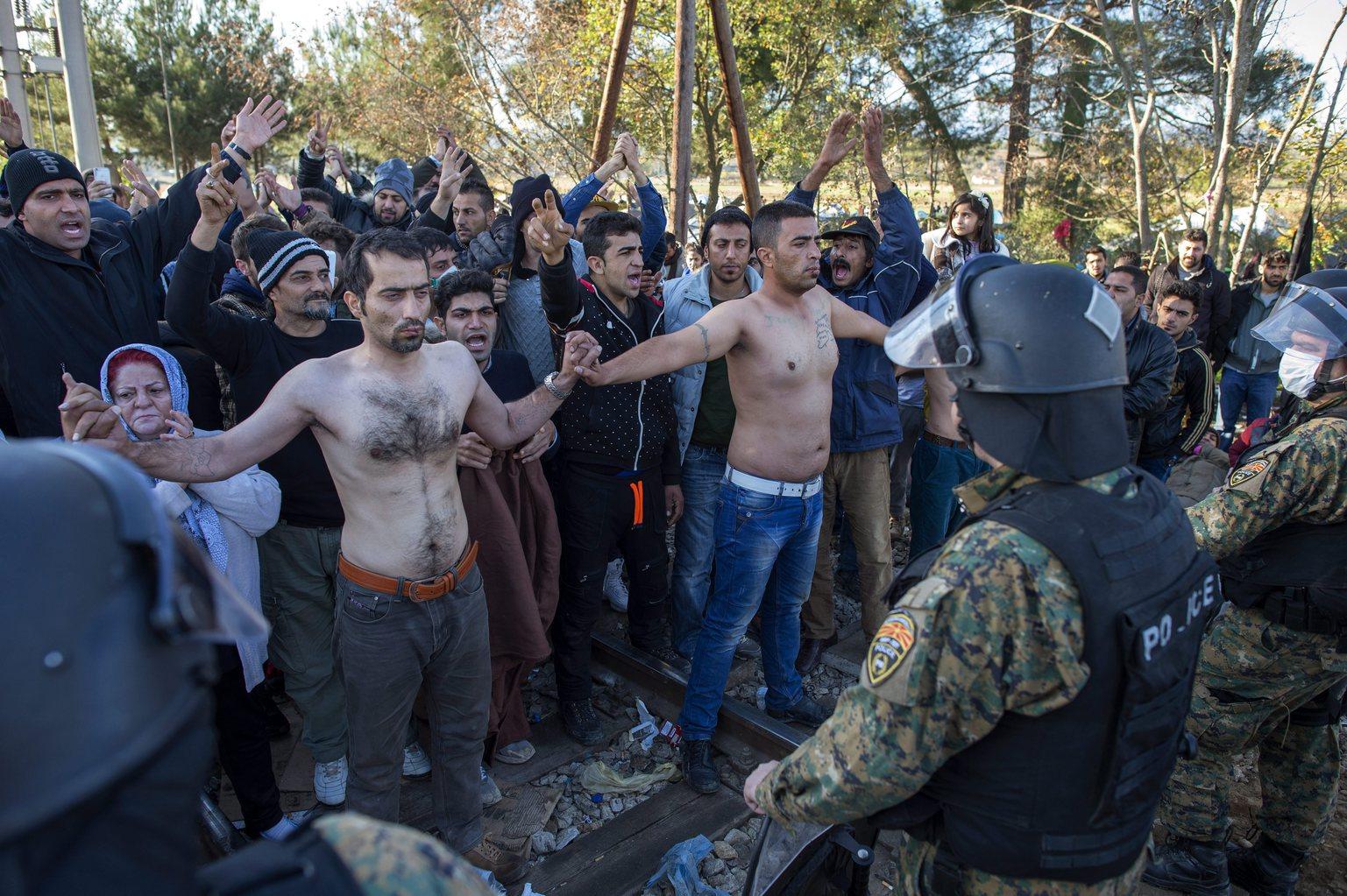 Félmeztelenre vetkőzött migránsok macedón rendőrök sorfala előtt a görög-macedón határon, az észak-görögországi Idomeni falu közelében 2015. november 23-án. Az Európai Unióba tartó illegális bevándorlók a továbbhaladásukért tüntetnek, mivel a macedón hatóságok napok óta csak a szíriai, iraki vagy afgán állampolgárokat engedik be az országukba. (MTI/EPA/Georgi Licovszki)