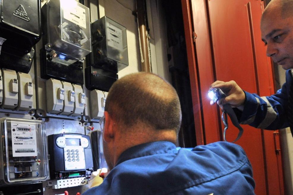 Budapest, 2012. március 12.Szalma Ferenc (háttal) és Papp Zsolt (j), az ELMŰ szakemberei előrefizetős árammérőt szerelnek fel egy budapesti társasházban.MTI Fotó: Máthé Zoltán