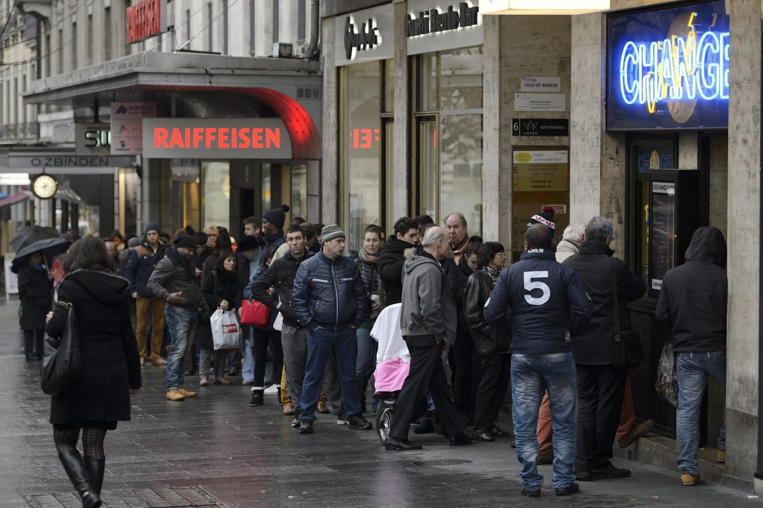 Sorban állnak az ügyfelek egy genfi pénzváltó előtt 2015. január 16-án. Az előző nap a svájci jegybank, a Svájci Nemzeti Bank eltörölte a svájci franknak az euróval szembeni árfolyamküszöbét, és az ez után megerősödő frank miatt a svájciaknak előnyös a frankjukat euróra váltani. (MTI/EPA/Martial Trezzini)