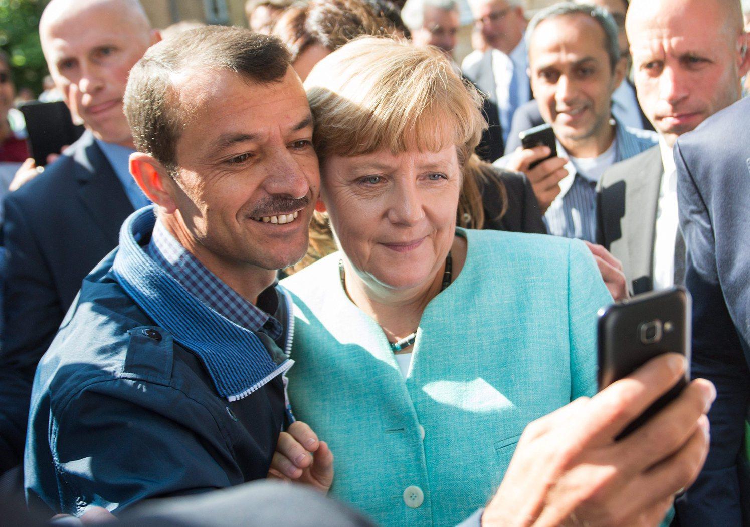 Angela Merkel német kancellárral (j) készít közös felvételt egy menekült a német szövetségi bevándorlás- és menekültügyi hatóság egyik berlini befogadó állomásán 2015. szeptember 10-én. (MTI/EPA/Bernd von Jutrczenka)