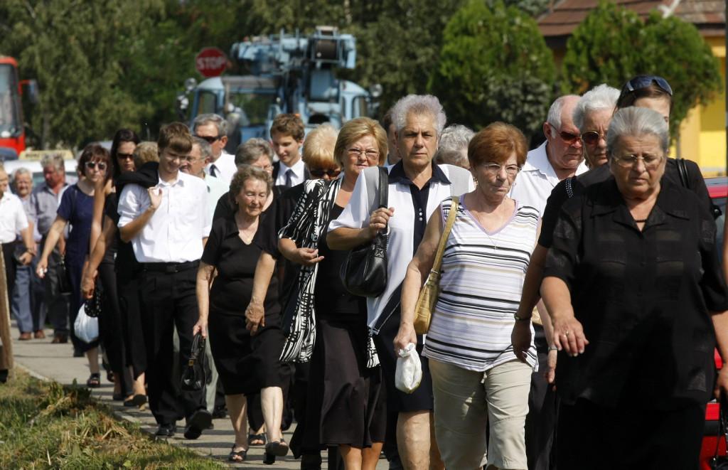 Miskolc, 2009. augusztus 26. Emberek érkeznek a miskolci paneltűz áldozatainak temetésére a szirmai temetőbe. Miskolcon, az Avas-déli városrész egyik tízemeletes épületében augusztus 15-én késő este ütött ki a tűz. Egy 39 éves nő és 13 éves fia füst-, illetve szénmonoxid mérgezésben a helyszínen, a család 16 éves lánya pedig három nappal később a kórházban halt meg. MTI Fotó: Vajda János