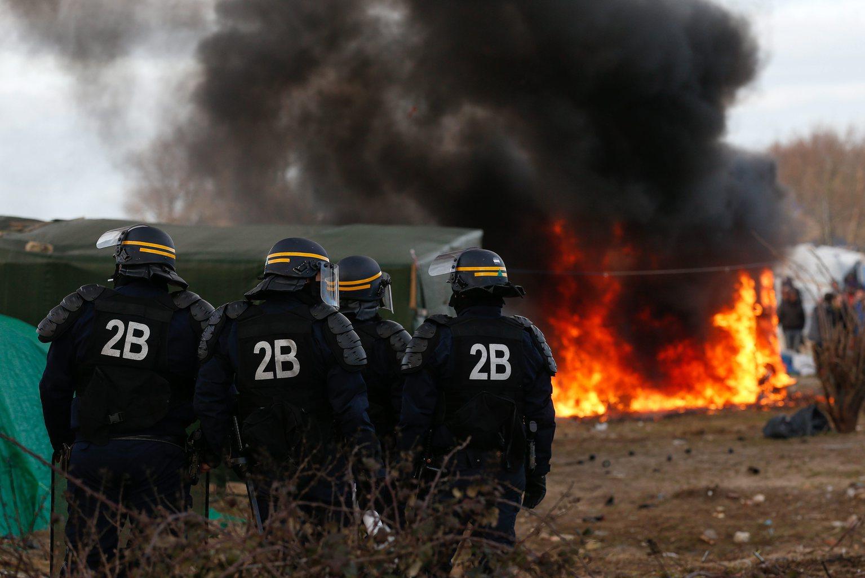Rohamrendőrök állnak a htéfőn felgyújtott calais-i sátortábor előtt (Fotó: EPA / Laurent Dubrule)