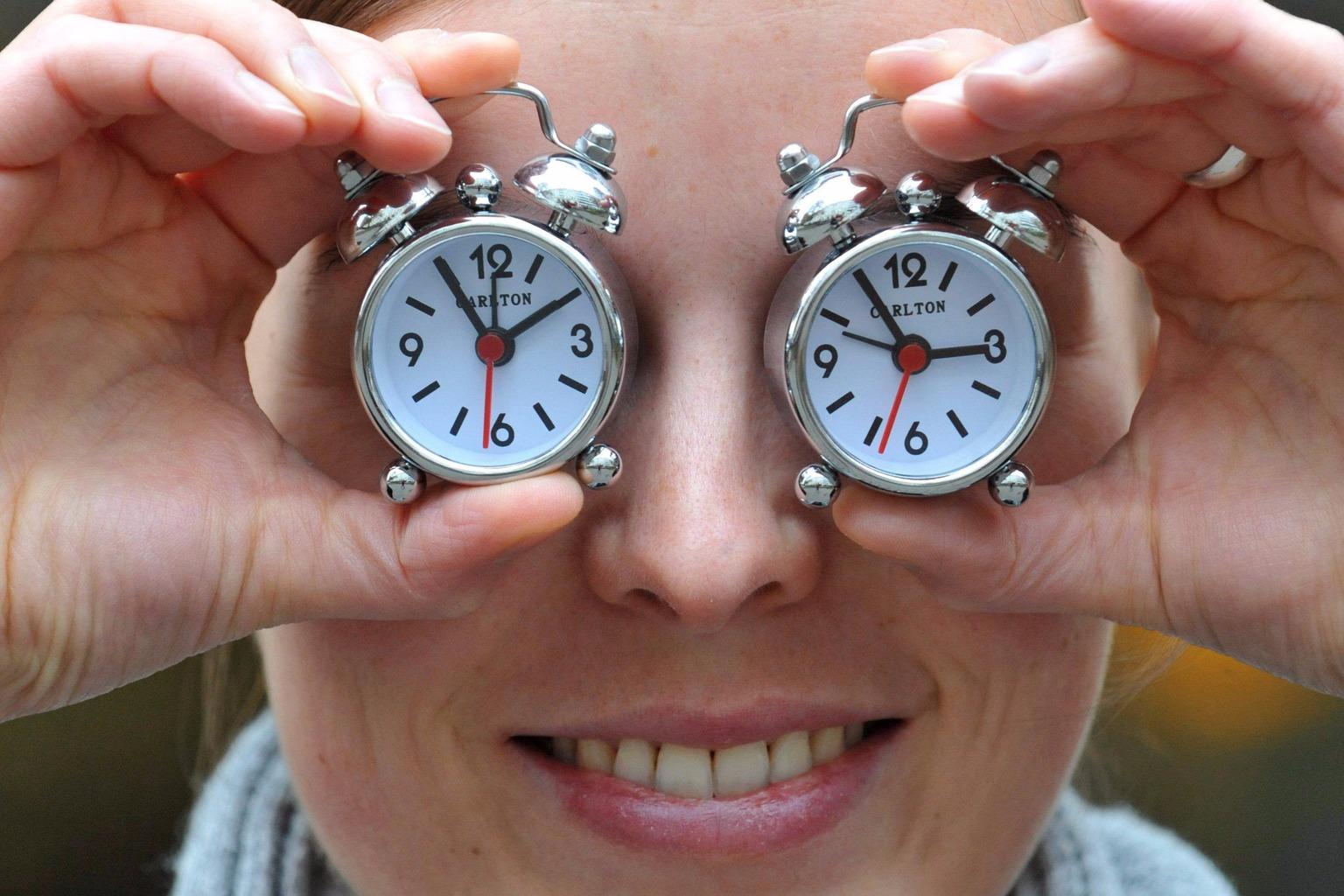 München, 2011. október 27. A világ legkisebb ébresztőóráit gyártó Carlton egyik alkalmazottja minivekkerekkel takarja el szemét a dél-németországi Münchenben 2011. október 27-én, hogy az óraátállítás napjának közeledésére figyelmeztessen. Európa országai a hónap utolsó vasárnapjára, az október 30-ra virradó éjszaka térnek vissza a téli időszámításhoz. (MTI/EPA/Andreas Gebert)