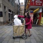 Egy nő tol egy bevásárlókocsit, benne Pepper, a japán SoftBank távközlési konszern egyik humanoid robotja a tokiói Omotesando bevásárlóutcában 2016. március 24-én. A cég újonnan nyílt üzletében, ahol az általuk kifejlesztett humanoid robotok szolgálják ki a vásárlókat, tíz darab Pepper nevű robot alkotja a személyzetet. Pepper a világ első olyan robotja, amely képes az emberek érzelmi reakcióinak és a testbeszéd olvasására. Az üzlet és robotszemélyzete március 30-ig fogadja a vásárlókat. (MTI/EPA/Franck Robichon)