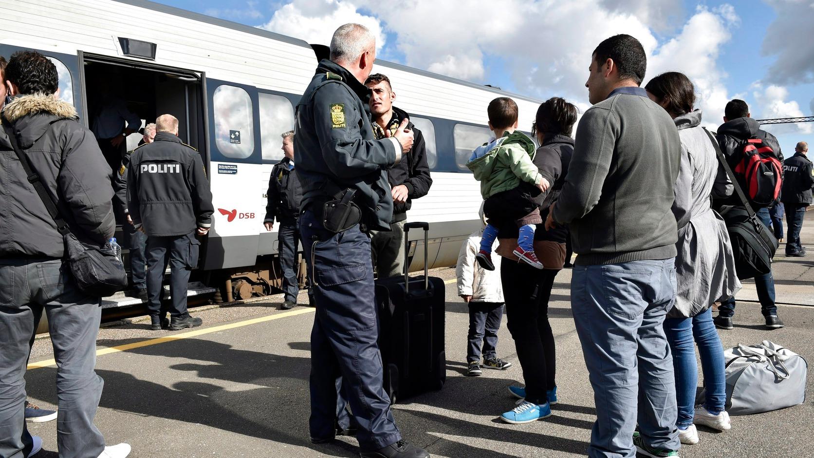 Rodby, 2015. szeptember 7. Migránsokkal beszél egy dán rendőr a dél-dániai Rodbyben 2015. szeptember 7-én. (MTI/EPA/Jens Noergaard Larsen)