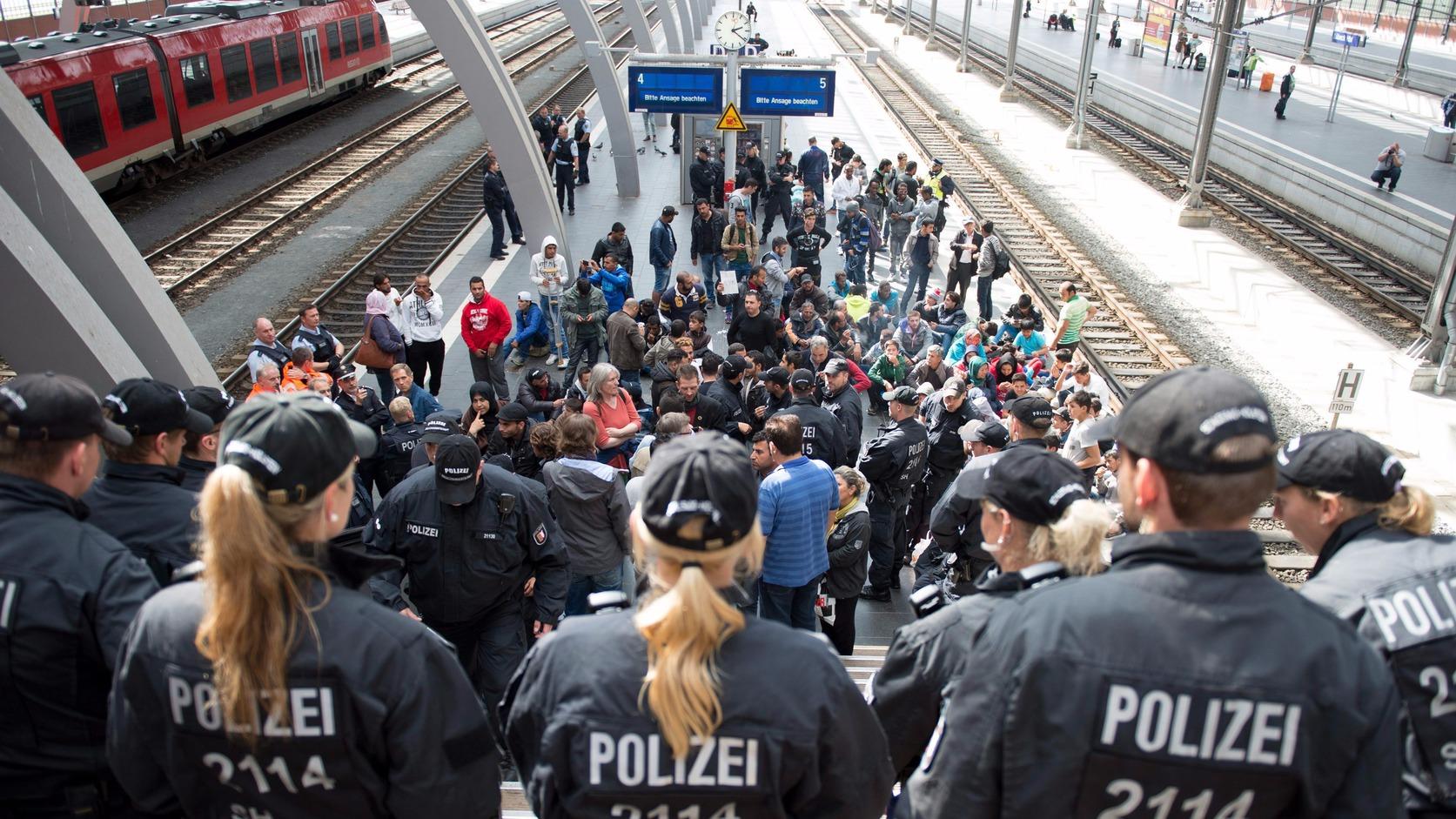 Svédországba tartó migránsok egy csoportja várakozik a lübecki vasútállomáson 2015. szeptember 8-án, miután rendőrök megállították őket. (MTI/EPA/Daniel Reinhardt)