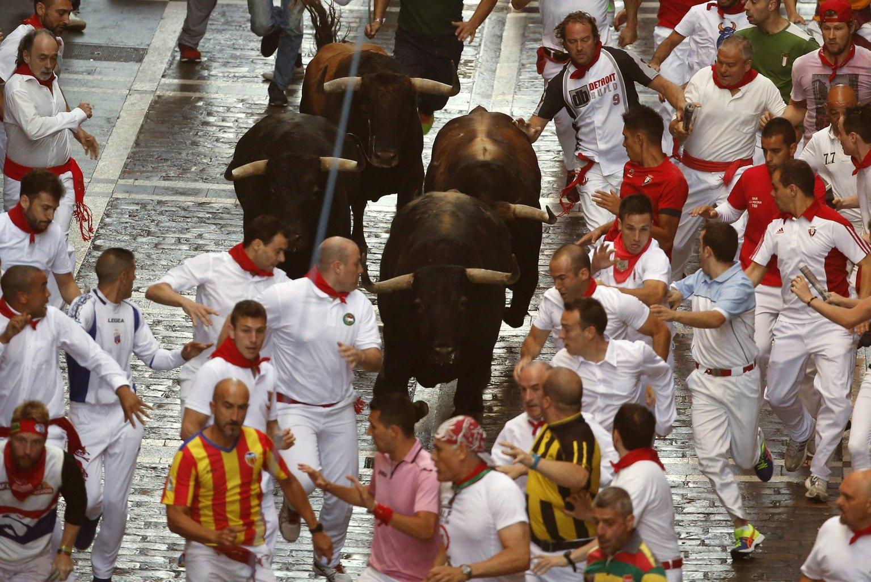 Résztvevők a San Fermín fesztivál bikafuttatásán Pamplonában 2015. július 7-én. A spanyol város védőszentjének tiszteletére 1591 óta évente megrendezett kilencnapos fiesta egyik fő attrakciója a reggelenkénti bikafuttatás, amelynek során férfiak százai teszik próbára bátorságukat azzal, hogy az arénába hajtott állatok előtt végigszaladnak Pamplona utcáin. (MTI/EPA/Javier Lizon)