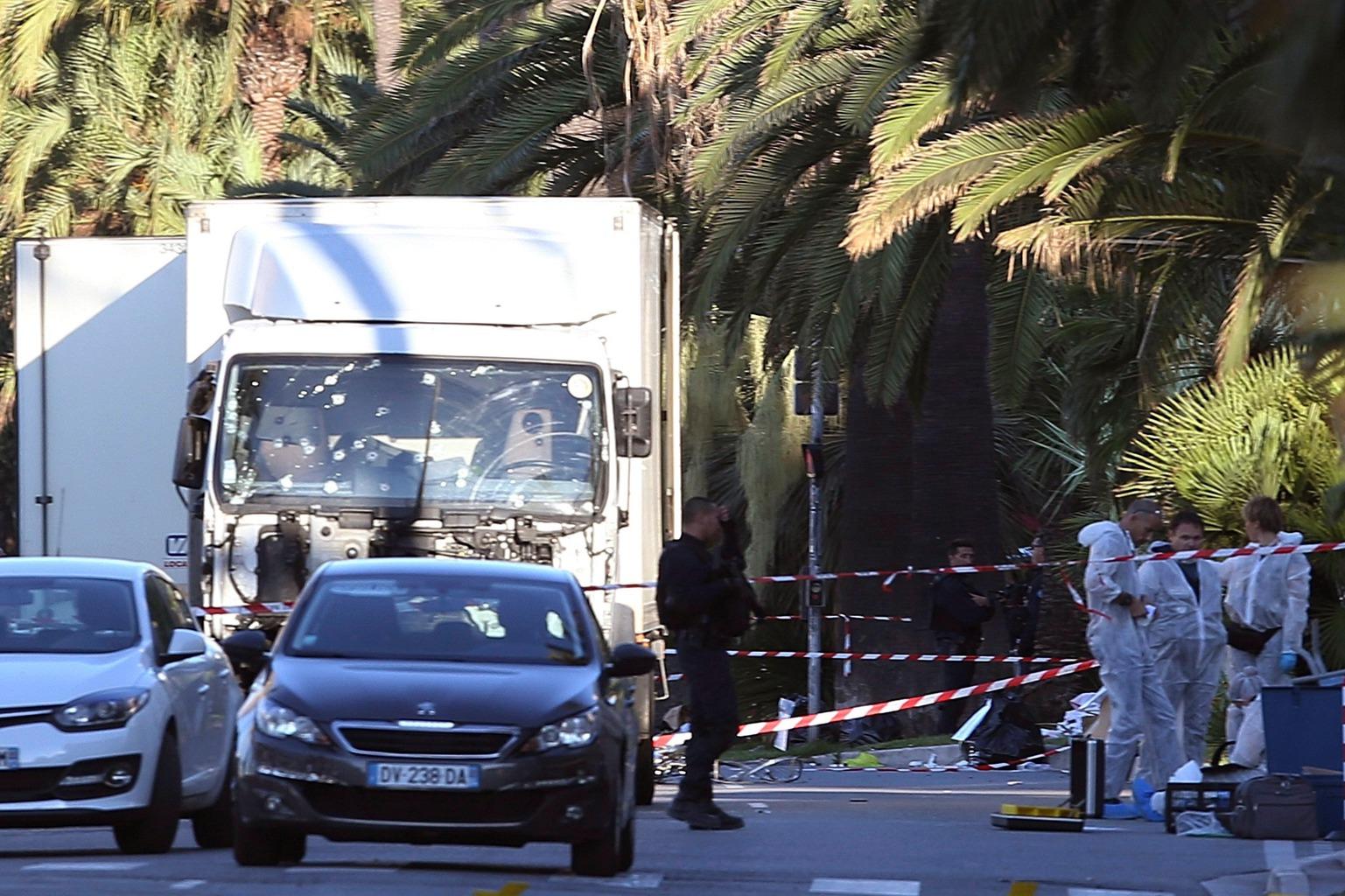 Nizza, 2016. július 15. Bűnügyi helyszínelők és egy gépfegyveres rendőr egy kilyuggatott szélvédőjű teherautónál, amellyel egy 31 éves tunéziai származású nizzai férfi belehajtott a tömegbe a nemzeti ünnep alkalmából rendezett tűzijáték idején a franciaországi Nizzában 2016. július 14-én este. Legkevesebb nyolcvannégyen életüket vesztették, mintegy hetvenen megsebesültek a gázolásban és az azt követő lövöldözésben, tizennyolc sebesült állapota válságos. A teherautó sofőrjét lelőtték. (MTI/AP/Luca Bruno)