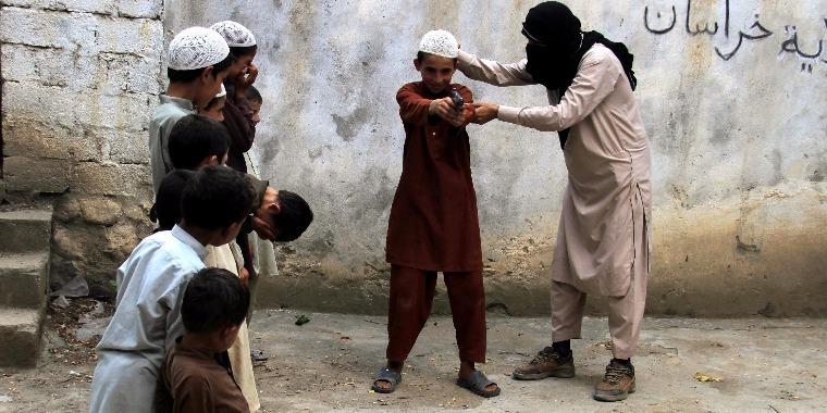 Az Iszlám Állam egyik tagja gyerekkel. (MTI/EPA/Gulamullah Habibi)