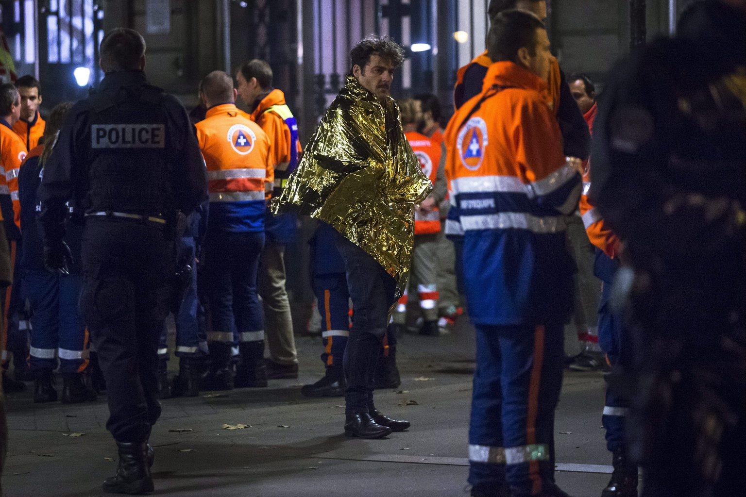 Egy kimenekített túlélő a párizsi Bataclan koncertterem közelében, miután az épületben mintegy száz embert túszul ejtettek 2015. november 13-án. A francia fővárosban késő este összehangoltan több merényletet követtek el. A támadásoknak legalább 120 halálos áldozata van. Nyolc terrorista halt meg, közülük heten felrobbantották magukat. (MTI/EPA/Etienne Laurent)