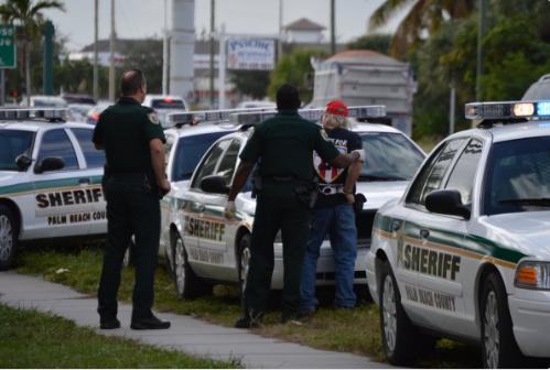 A 68 éves férfit bilincsben vitték el a rendőrök a szavazóhelyiség elől (Fotó: Twitter)