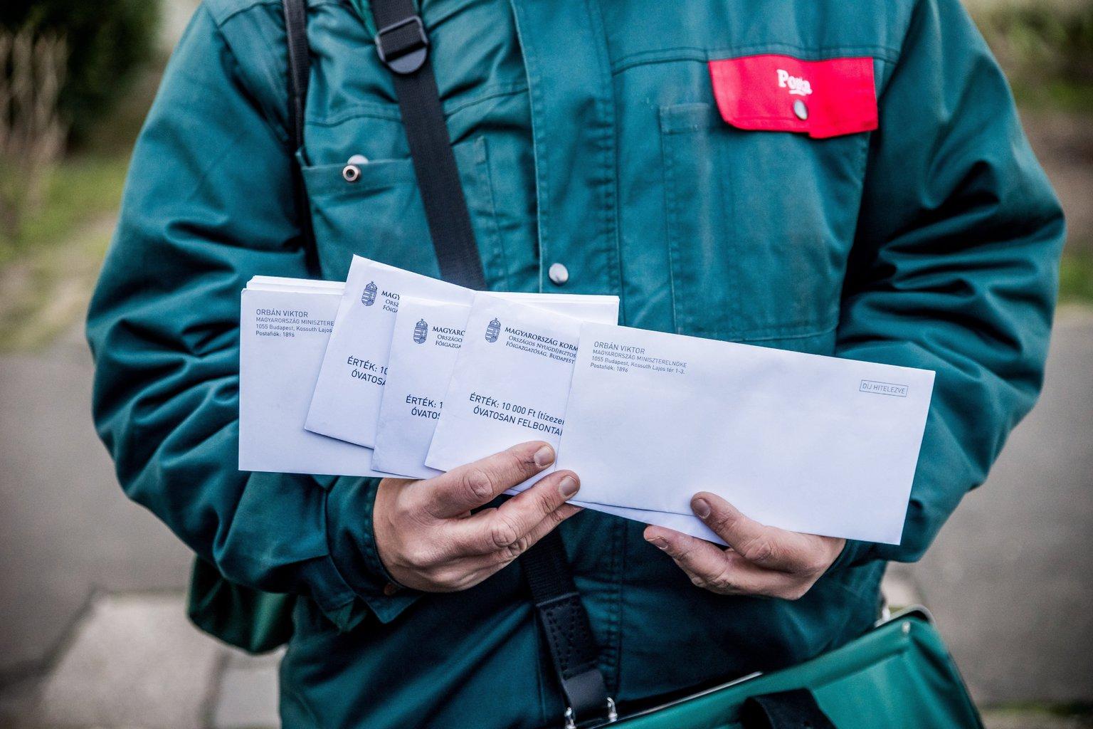 A Magyar Posta Zrt. munkatársa mutatja a nyugdíjasoknak kézbesítendő Erzsébet-utalványokat tartalmazó borítékokat és Orbán Viktor miniszterelnök köszöntő levelét (MTI Fotó: Balogh Zoltán)