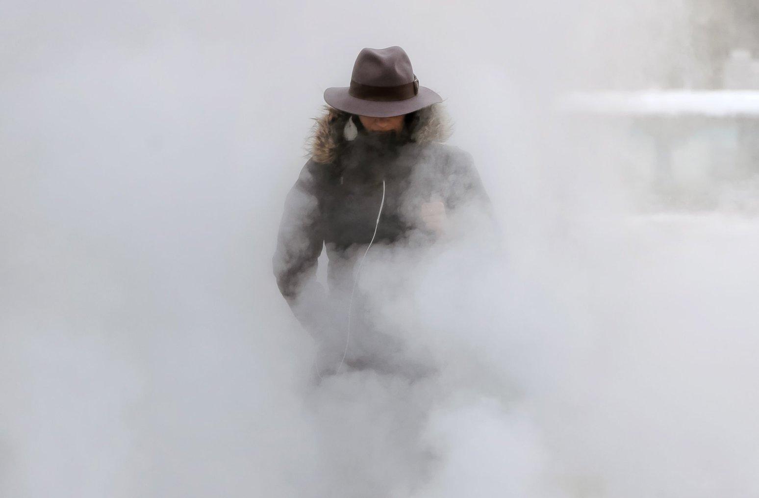 Föld alatti szellőztetőből feltörő gőzfelhőben egy nő Bukarestben 2017. január 10-én, amikor a levegő hőmérséklete -20 Celsius-fok alá süllyedt a román fővárosban (MTI/AP/Vadim Ghirda)