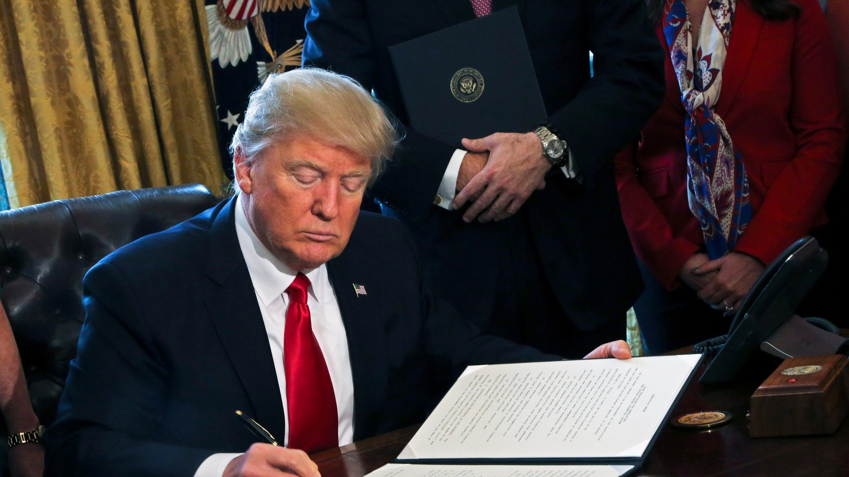 epa05769604 US President Donald J. Trump signs an executive order in the Oval Office of the White House, in Washington, DC, USA, 03 February 2017. Trump signed several executive orders including an order to review the Dodd-Frank Wall Street to roll back financial regulations of the Obama era.  EPA/Aude Guerrucci / POOL