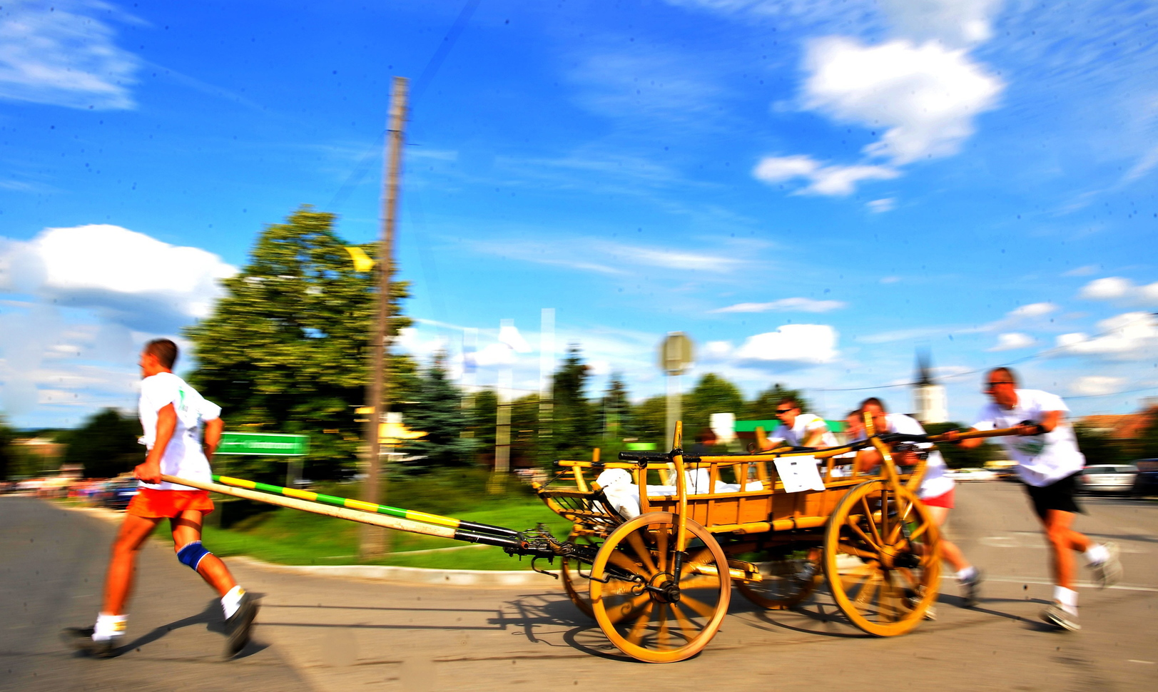 Kocs, 2009. július 12. A Tatai Ászok Gondűző csapata rohan a szekérrel a 11. kocsitoló versenyen Kocson. A hagyományos viadalra nevezett 20 férfi és két női csapatnak a falu dimbes-dombos főutcáján, 1800 méter hosszú távon időre kell végigtolnia egy 380 kilós szekeret. A Komárom-Esztergom megyei községben, annak emlékére rendezik meg a versenyt, hogy annak emlékére, hogy a gyors és könnyű szekeret a feljegyzések szerint a település kisiparosai fejlesztették ki az 1200-as években. MTI Fotó: Illyés Tibor