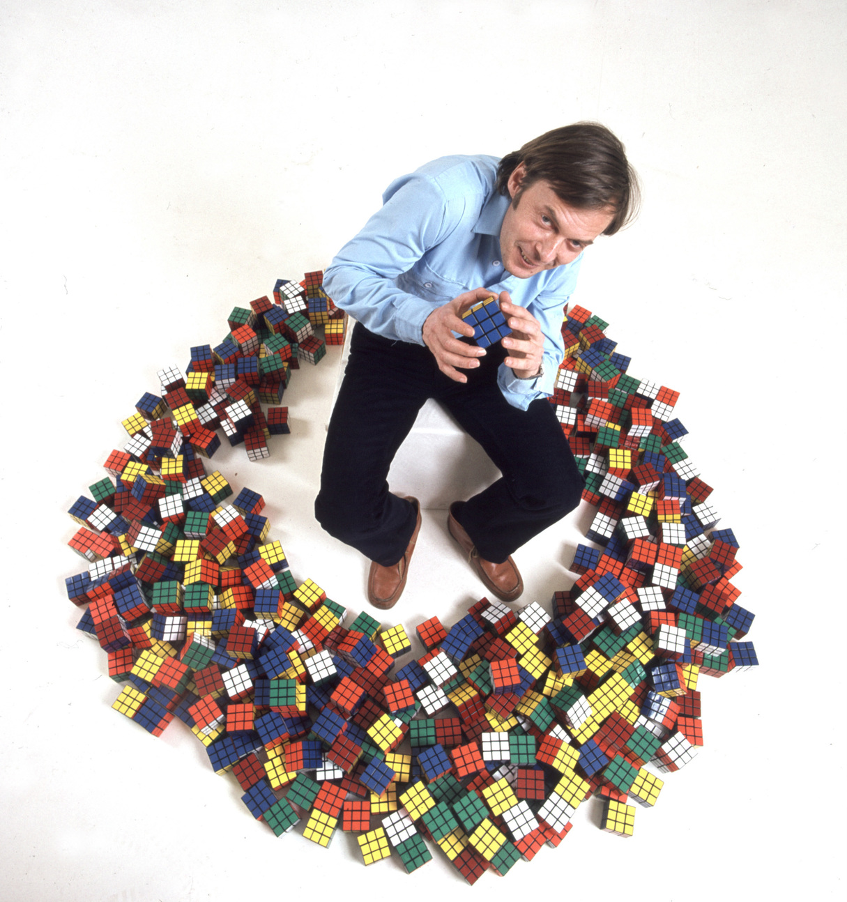 """Budapest, 1981. február 25. Ifj. Rubik Ernő építész, tárgytervező, a világhíres """"bűvös kocka"""" és több más logikai játék feltalálója kockáinak """"körében"""", egy reklámfotón. MTI Fotó: Tóth Gyula"""
