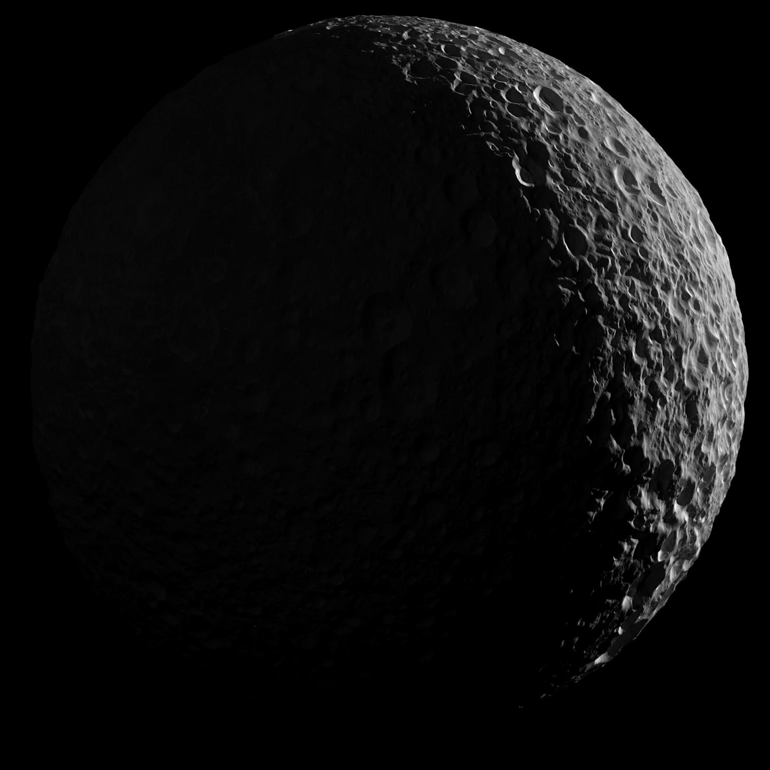 A Mimasz, ahogyan nagy teljesítményű teleszkópon keresztül látnánk, bal féltekéje árnyékban, alig világítja meg a Szaturnusz visszaverte fény. (Fotó: NASA/JPL-Caltech/Űrtudományi Intézet)