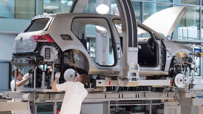 A Volkswagen német járműgyártó egyik e-Golf elektromos autóját szerelik össze alkalmazottak a drezdai Üvegfalú Gyárban, a Gläserne Manufakturban 2017. április 3-án, a modell tömeggyártásának hivatalos kezdőnapján. (MTI/AP/Jens Meyer)