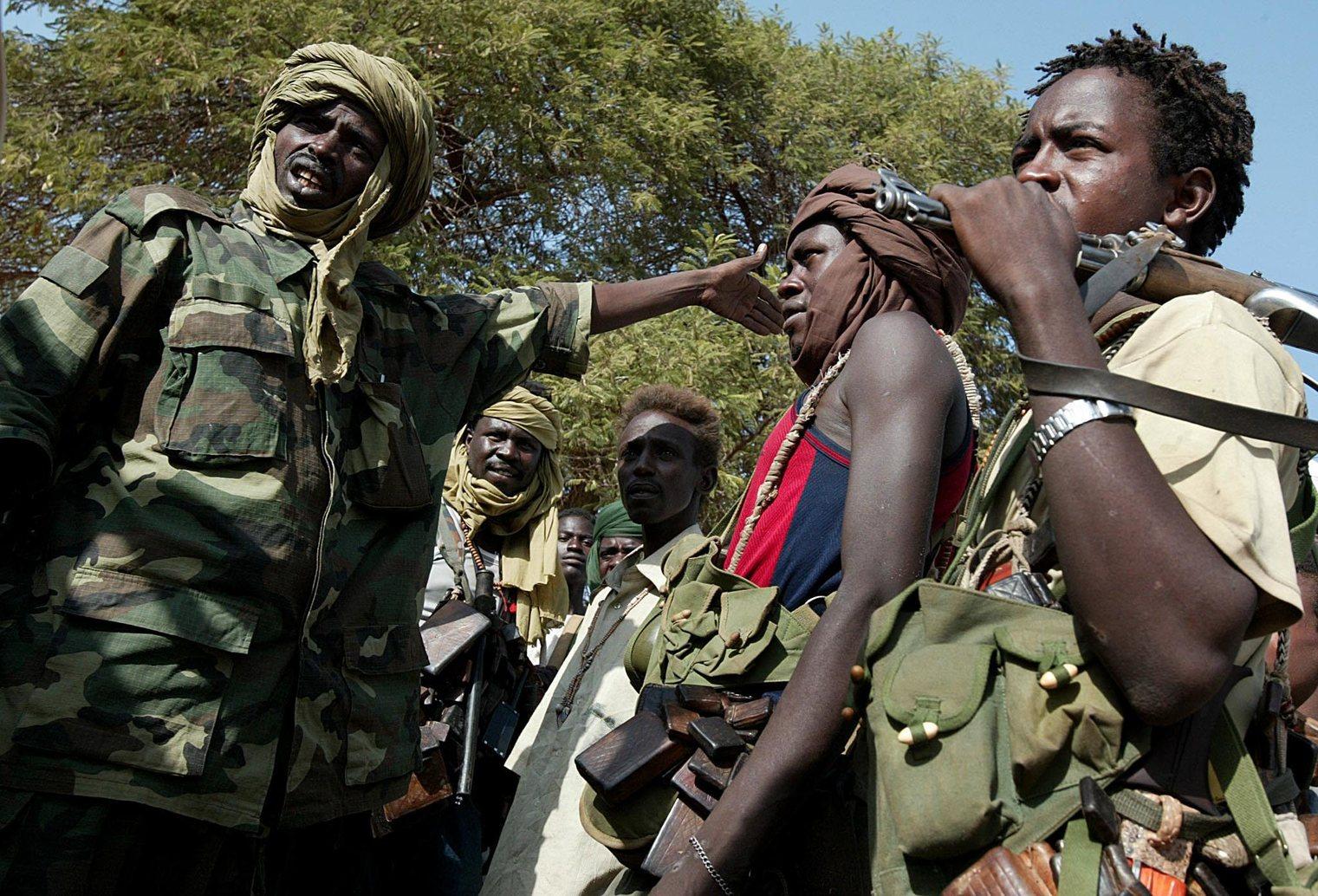 Az Igazság és Egyenlőség Mozgalma (JEM) nevű szudáni lázadó csoport fegyverese (b) a Szudáni Felszabadítási Hadsereg (SLA) harcosaival beszéli meg a hadműveleti tervet a szudáni Dárfúr tartomán yészaki részében fekvő el-Lajit város közelében 2004. október 24-én. A JEM és az SLA vállvetve próbálja útját állni a szudáni kormányhadsereg előrenyomunlásának Dárfúr északi részén. A kormány légiereje október 19. óta minden éjjel bombázza el-Lajitot, a város lakosságának többsége pedig a felkelők ellenőrizte környező falvakba menekült. (MTI/EPA/Nic Bothma)