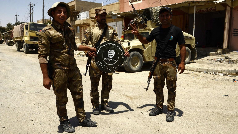 Iraki katonák az Iszlám Állam dzsihadista terrorszervezet zászlójával Moszul egyik nyugati negyedében, Sifában 2017. június 17-én - az iraki hadsereg közlése szerint 2017. június 18-án az iraki erők megkezdték az előrenyomulást Moszul dzsihadisták kezén lévő óvárosában (Fotó: MTI/EPA/Omar Alhajali)