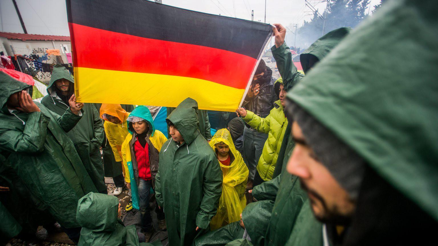 Demonstráló migránsok német zászlóval a görög-macedón határ görög oldalán, Idomeniben (MTI Fotó: Balogh Zoltán)