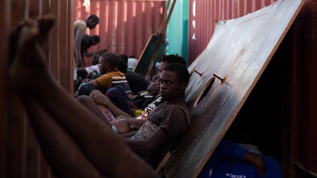 Líbiai haditengerészek által a Földközi-tengerből, a líbiai partok előtt kimentett migránsok Tripoli kereskedelmi kikötőjében - a 112 embert őrizetbe vették (Fotó: MTI/EPA)