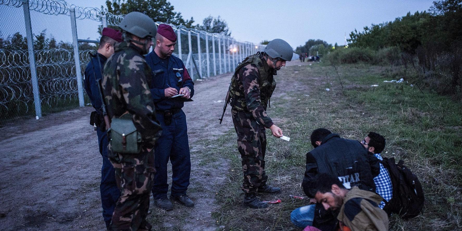 Katonák és rendőrök három elfogott illegális bevándorlót őriznek a biztonsági határzár mellett a szerb-magyar határon, Röszke térségében 2015. szeptember 15-én. (MTI Fotó: Ujvári Sándor)