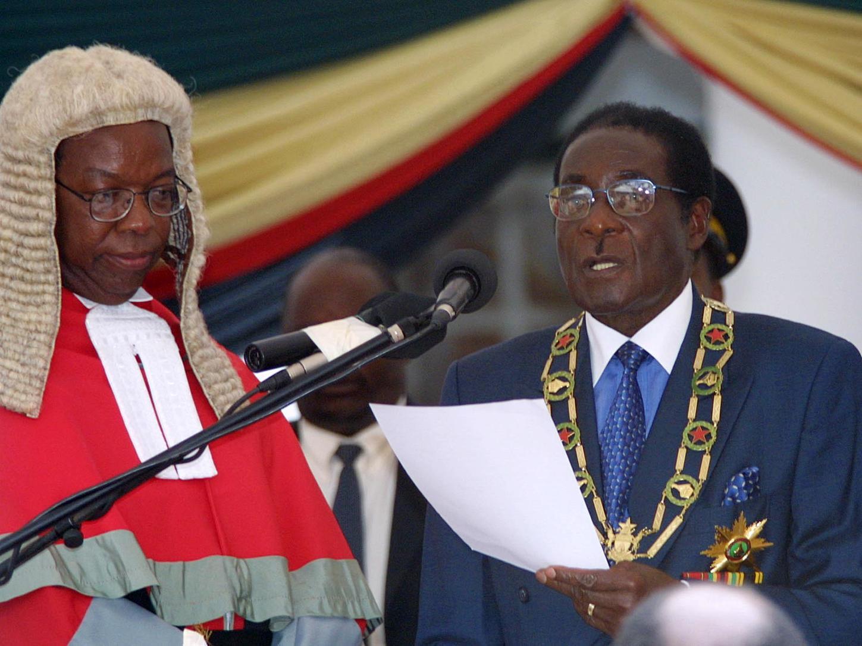Robert MUGABE zimbabwei  elnök, a 22 éve hatalmon lévő Zimbabwei Afrikai Nemzeti Unió-Hazafias Front (ZANU-PF) párt elnöke  (j) leteszi hivatali esküjét  a Hararében tartott beiktatási ünnepségen 2002. március 17-én. Az ellenzék szerint csalással  újraválasztott  Mugabe az eskütételt követő beszédében a földreform gyorsítását ígérte meg népének.  A földreform tízmillió hektár fehérek tulajdonában lévő föld  kisajátítását és nincstelen feketék közötti szétosztását irányozza elő.  (MTI FOTÓ/ EPA/AFPI/ALEXANDER JOE)