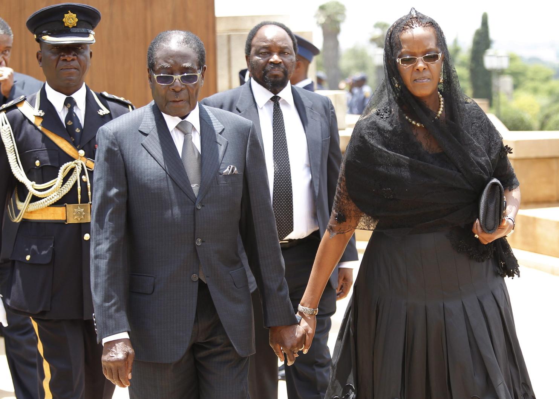 Pretoria, 2013. december 11. Robert Mugabe zimbabwei elnök és a felesége, Grace, miután lerótták kegyeletüket Nelson Mandela Nobel-békedíjas volt dél-afrikai elnök ravatalánál a kormány központját és az elnöki hivatalt magába foglaló pretoriai Unió épületeknél 2013. december 11-én. A Dél-afrikai Köztársaság első fekete bőrű államfője december 5-én, 95 éves korában hunyt el. (MTI/EPA/Kim Ludbrook)