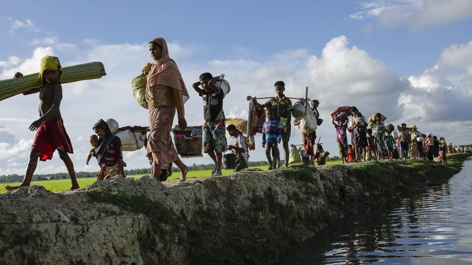 Mianmari rohingja családok holmijukkal gyalogolnak a bangladesi Naf folyó partján, Palongkhali térségében 2017. október 9-én. Az augusztus 25-i arakáni erőszakhullám elől több mint félmillió muszlim rohingja menekült el a többségében buddhisták lakta Mianmarból. A Nemzetközi Migrációs Szervezet, az IOM szerint mintegy 300 ezer menekült a szabad ég alatt száll meg. (MTI/EPA/Abir Abdullah)