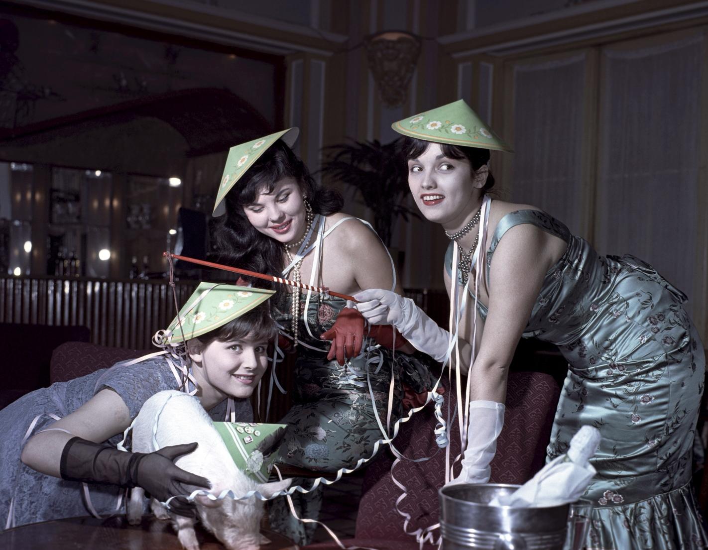 Magyarország, 1960. december 31. Modellek mosolyogva pózolnak egy, az új évben szerencsét hozó szilveszteri kismalaccal. A felvétel készítésének pontos helye ismeretlen. MTI Fotó: Bajkor József