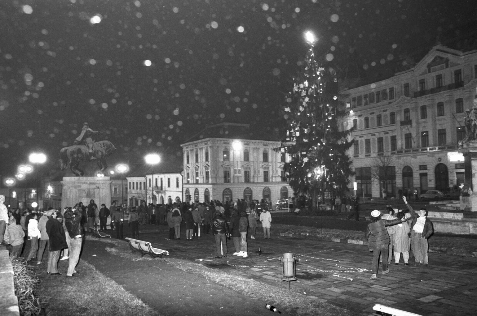 """Pécs, 1989. december 31. Az új évet ünneplők jókedvű csoportjai éjfél után a város karácsonyfájánál. Vidáman, jó hangulatban búcsúztatták az óévet Pécs lakói. A szórakozóhelyeken teltház volt, a nevesebb éttermekben már egy hónappal korábban lefoglaltak minden helyet a hazai és külföldi vendégek. A koccintást követően még sokan ünnepeltek a Széchenyi téren álló """"mindenki"""" karácsonyfája körül. MTI Fotó: Kálmándy Ferenc"""