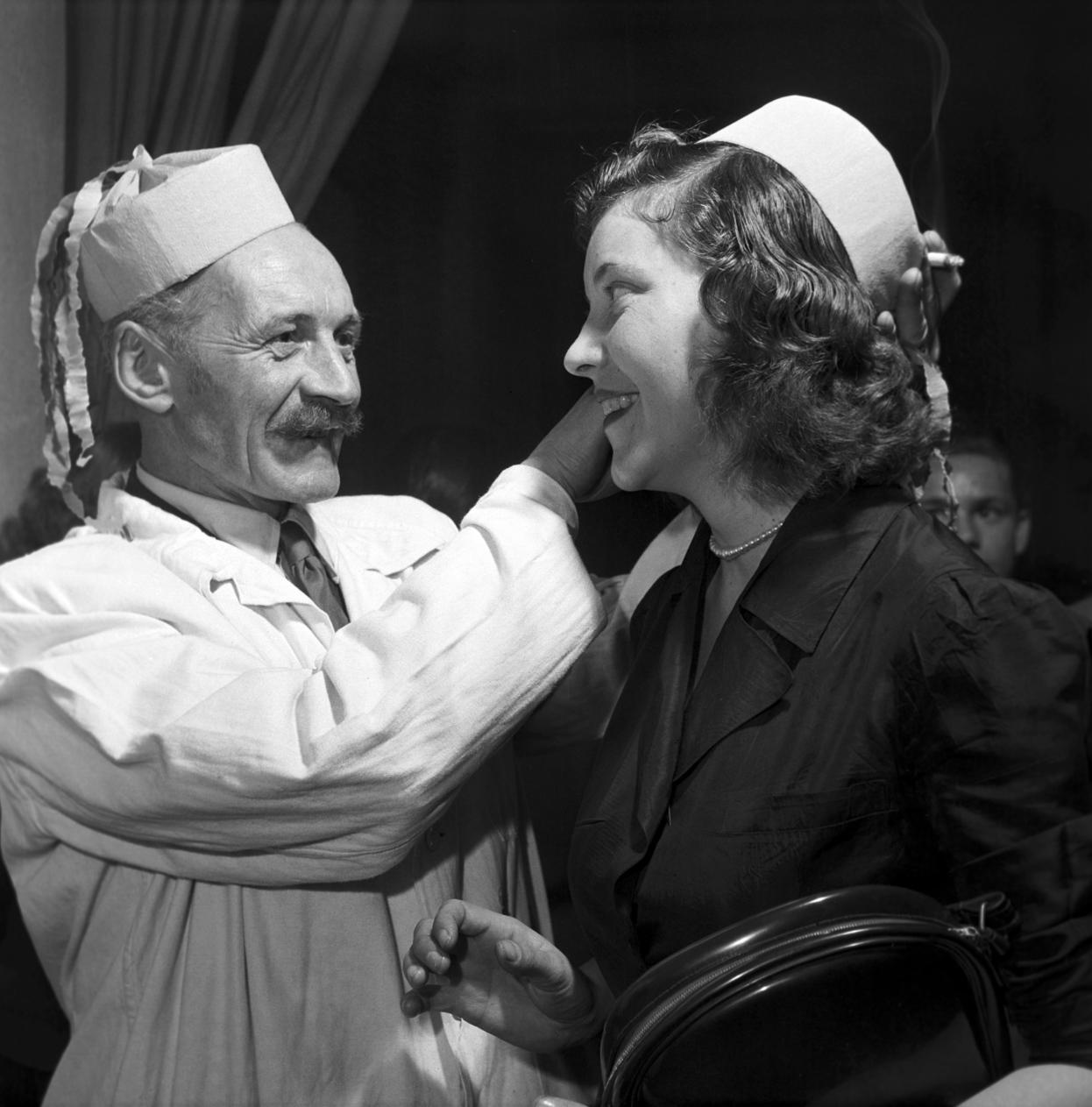 Miskolc, 1958. január 1. A miskolci Avas Szálló egyik munkatársa megigazítja egy női vendég szilveszteri kalapját. MTI Fotó: Bereth Ferenc