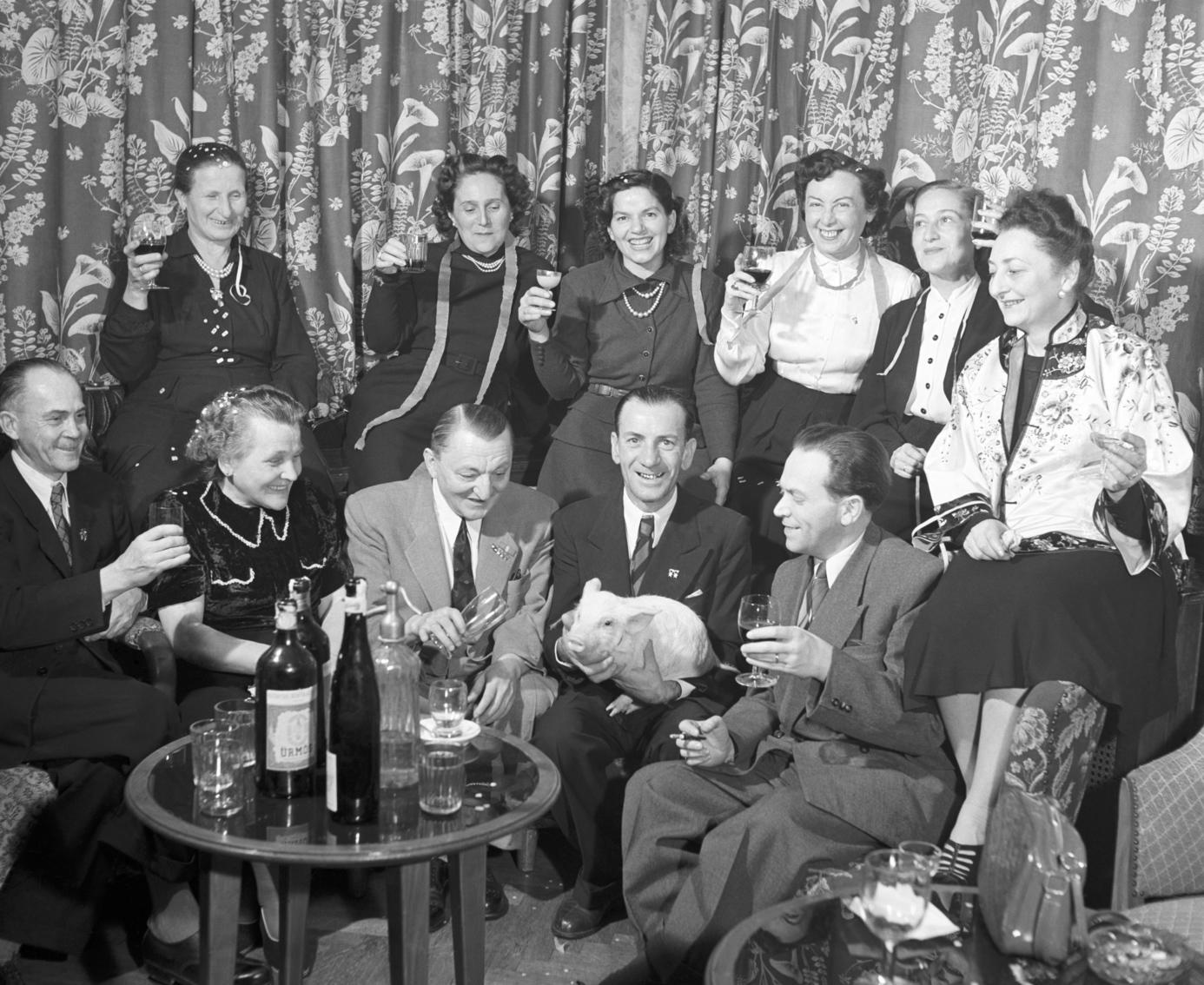 Galyatető, 1954. január 2. Rossz Károly (első sor b1), a XII/1 Épületüvegező Vállalat kétszeres sztahanovista üvegszabásza, Kónyai Kiss Albertné (első sor b2), Kónyai Kiss Albert (első sor k), a Vörös Csillag Nyomda háromszoros sztahanovista gépszedője, a Szocialista Munka Érdemérem tulajdonosa, Krinyák Géza (első sor j2), a Faipari Szerszámkészítő Vállalat kétszeres sztahanovista gépmunkása (malaccal a kezében), Földes Iván (első sor j1), a Földművelésügyi Minisztérium osztályvezetője, a Népköztársasági Érdemérem ezüst fokozatának tulajdonosa, Kasztl Árpádné (hátsó sor j3), a Május 1. Ruhagyár sztahanovista dolgozója és Marton Istvánné (hátsó sor j1), a Papíripari Kutatóintézet munkaérdemrendes vegyésze nagy társaságban szilvesztereznek a galyatetői SZOT üdülőben. MTI Fotó/Magyar Fotó: Járai Rudolf