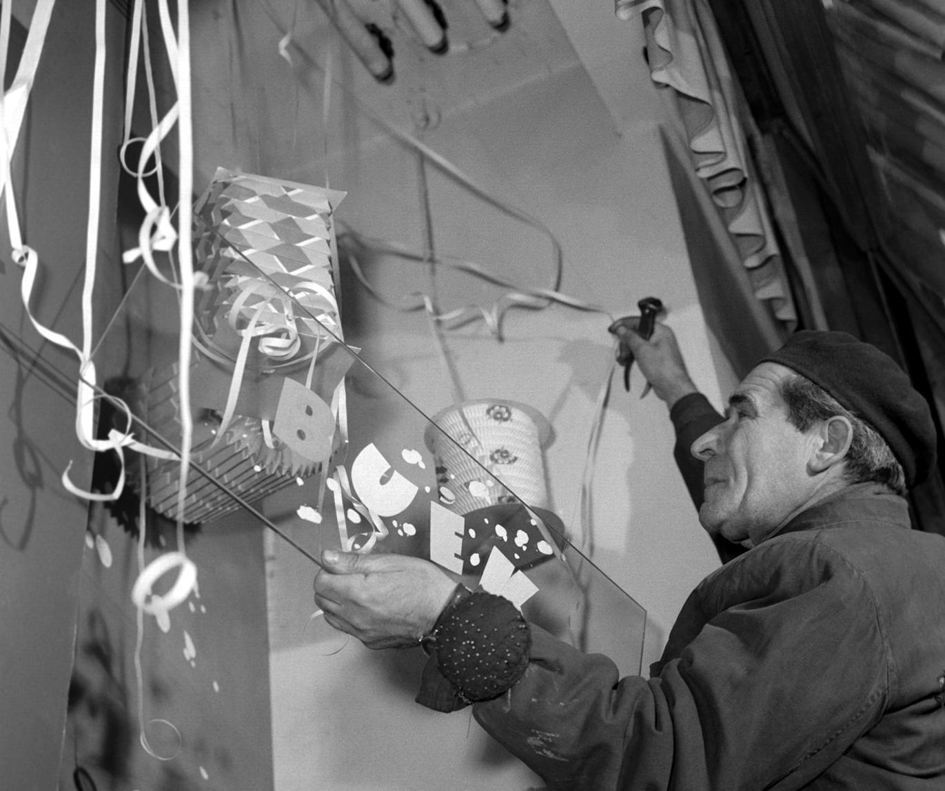 Budapest, 1960. december 27. Egy kirakatrendező a BÚÉK (Boldog új évet kívánok!)feliratú táblát szereli fel egy üzlet kirakatában.  MTI Fotó: Pálfai Gábor