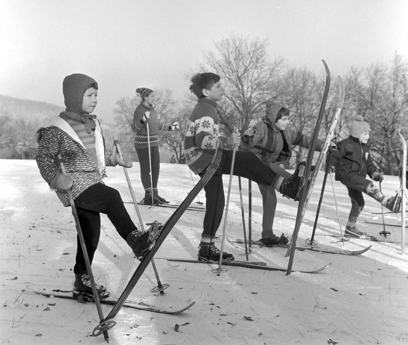 Budapest, 1968. január 4. Egyensúly-gyakorlatot végző sí-iskolások a Normafánál. A téli szünetben hetente egyszer síoktatást tartanak az érdeklődő kisdiákoknak Szabó Zoltán testnevelő tanár vezetésével. MTI Fotó: Patkó Klári