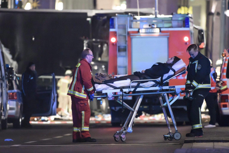 Sebesültet visznek hordágyon tűzoltók egy berlini karácsonyi vásárban 2016. december 19-én, miután egy férfi egy lopott lengyel kamionnal a vásárlók közé hajtott. A merényletben legkevesebb tizenketten életüket vesztették és negyvennyolcan megsebesültek, a vezetőfülkében megtalálták a kamion lengyel sofőrjének holttestét. (MTI/EPA/Clemens Bilan)