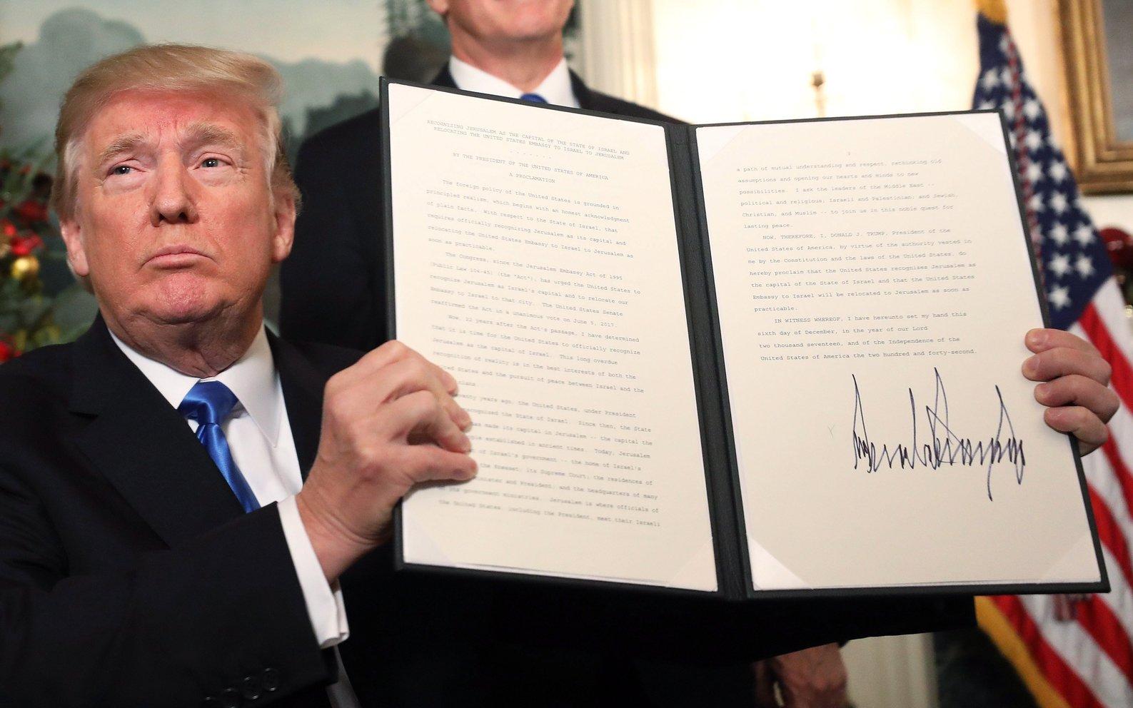 Donald Trump amerikai elnök mutatja az általa aláírt, Jeruzsálemet Izrael fővárosaként elismerő dekrétumot Mike Pence alelnök jelenlétében a washingtoni Fehér Házban 2017. december 6-án. (MTI/AP/Evan Vucci)