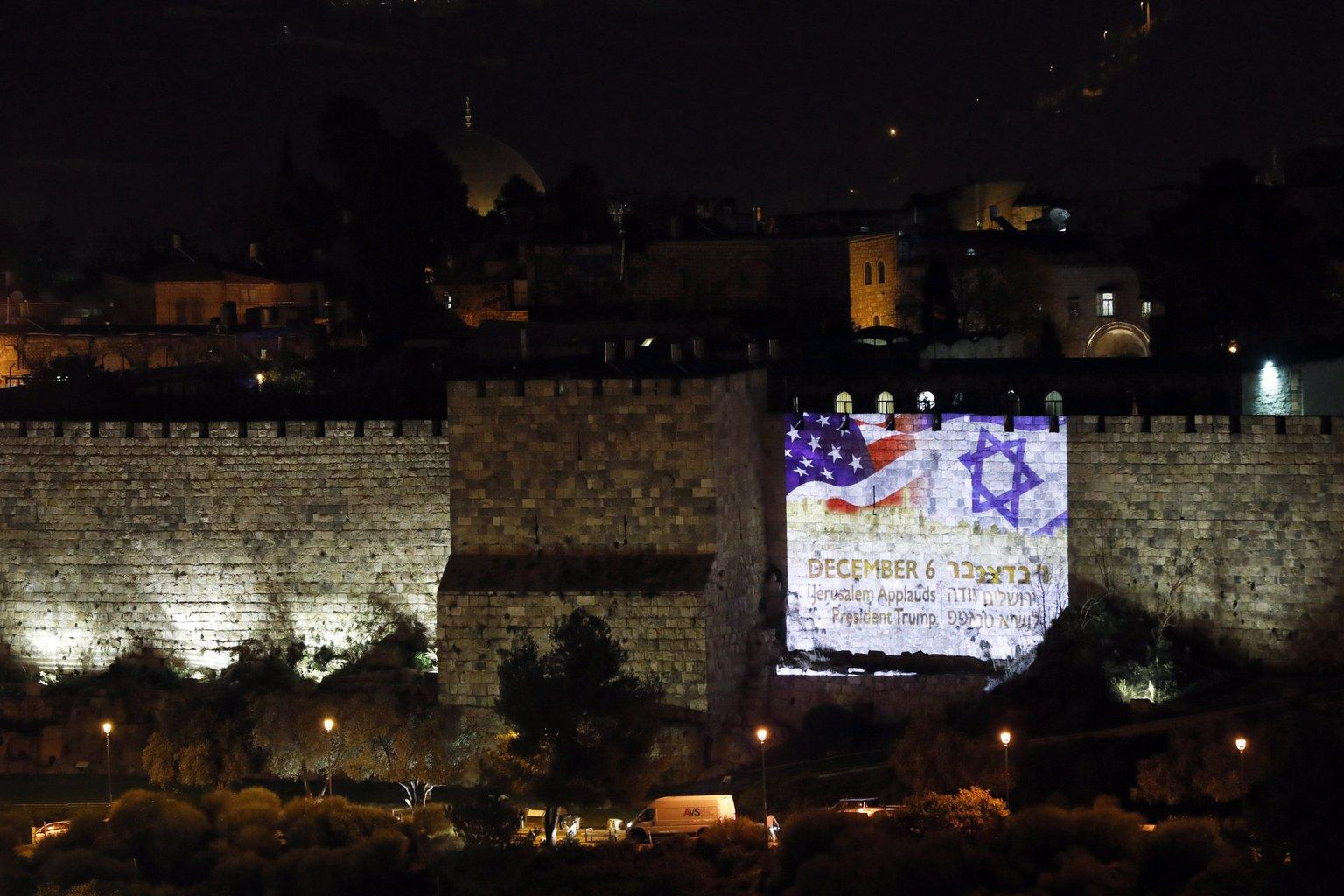 Az izraeli és az amerikai zászlót veítik a jeruzsálemi Siratófalra, miután Donald Trump amerikai elnök aláírta a Jeruzsálemet Izrael fővárosaként elismerő dekrétumot 2017. december 6-án. A fényfestésen álló felirat jelentése: Jeruzsálem megtapsolja Trump elnököt. (MTI/EPA/Abir Szultan)