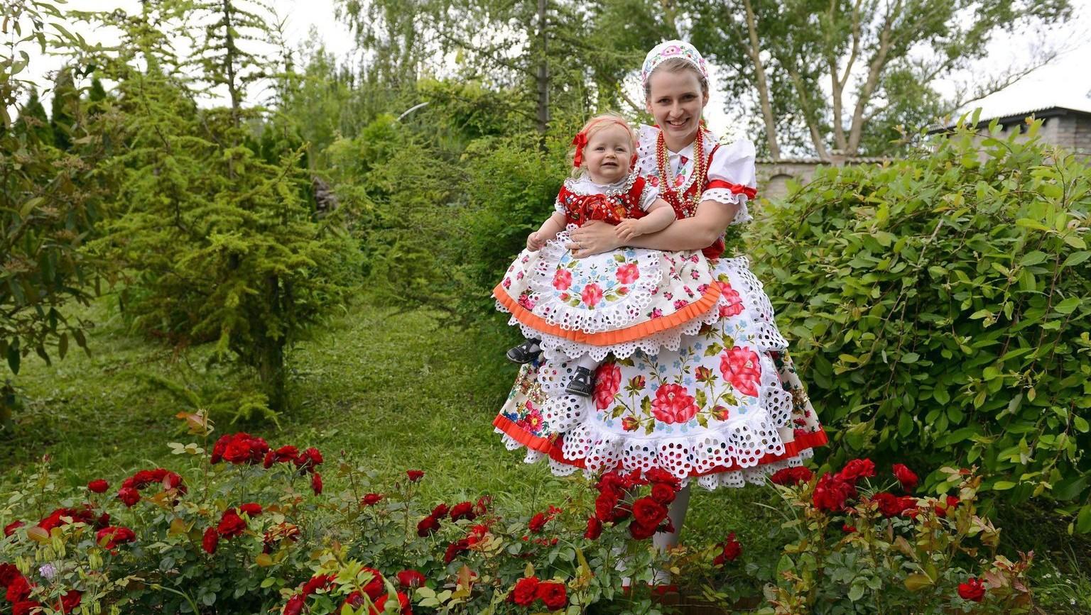 Molnár Lajkó Anett és egyéves lánya, Manna gombosi népviseletben házuk kertjében, a vajdasági Gomboson 2015. május 27-én – képünk illusztráció (MTI Fotó: Molnár Edvárd)