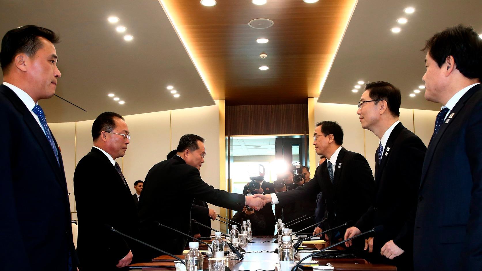 Panmindzson, 2018. január 9. Cso Mjung Gjon, országegyesítési ügyekért felelős dél-koreai miniszter (j3) és Li Szon Gvon, az észak-koreai delegáció vezetője (b3) kezet fog a februári dél-koreai téli olimpián való észak-koreai részvételről tartott tárgyaláson a két Koreát elválasztó panmindzsoni demilitarizált övezet dél-koreai oldalán levő Béke Házában 2018. január 9-én. A felek megállapodtak abban, hogy Phenjan sportolókat, magas rangú tisztviselőket és szurkolókat küld a téli olimpiára. A megbeszélés több mint két éve az első hivatalos találkozó a két ország között. (MTI/EPA pool/Jang Uj Csel)