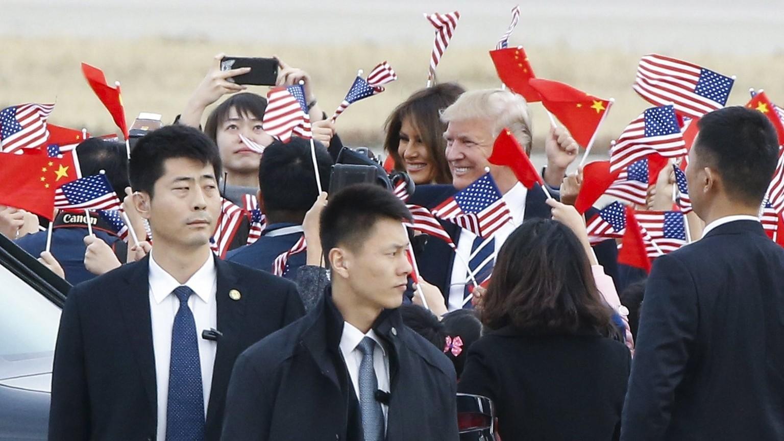Amerikai zászlókkal köszöntik Donald Trump amerikai elnököt és nejét, Melania Trumpot a pekingi repülőtéren 2017. november 8-án (Fotó: MTI/EPApool/Thomas Peter)